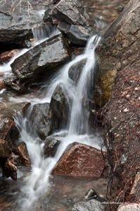 Melting snow creates small streams crashing over rocks and boulders gaining strength, power and freedom.